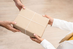 Woman hands receiving package from a man Royalty Free Stock Photography