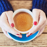 Woman hands with red manicure and cup of coffee Stock Images
