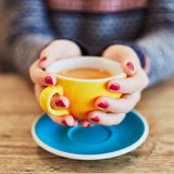 Woman hands with red manicure and cup of coffee Stock Photography