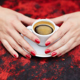 Woman hands with red manicure and cup of fresh hot coffee Stock Image