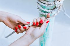 Woman hands with red manicure holding rope outdoors Stock Photo
