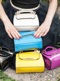 Woman hands resting on colored bags. Many colorful purses Royalty Free Stock Images