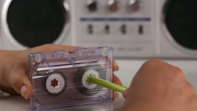Woman hands rewind an audio cassette using a pen, closeup. Woman hands rewind an audio cassette using a pen - retro player in background, camera zooming or stock video