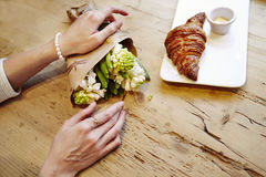 Woman hands with ring on finger, hyacinth bouquet flowers, romantic date in cafe, breakfast with croissant and coffee. St. Valenti Stock Image
