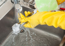Woman hands rinsing cutlery under running water stock photo