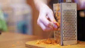 Woman Hands Rubbing Carrots on Grater in a Home Kitchen. Slow Motion stock video footage