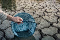 Woman hands are scooping water on cracked ground. royalty free stock image