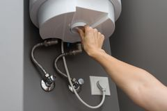 Woman hands setting temperature of water in heater electric boiler. Interior details close-up. royalty free stock photo