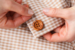 Woman Hands sewing button on fabric Stock Images