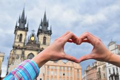 Woman hands show heart over Prague cityscape. Close up young woman hands showing heart shape love symbol over cityscape with Cathedral of Our Lady before Tyn Royalty Free Stock Photos
