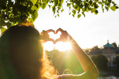 Woman hands showing shape of a heart on sunset, young woman travel alone, love concept Stock Photos