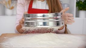 Woman hands sifting flour onto wooden board in the kitchen. Camera slide, slow motion stock footage