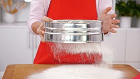 Woman hands sifting flour onto wooden board in the kitchen. Camera tilt down, slight slow motion stock video