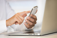 Woman hands with smart phone and computer keyboard Stock Photos