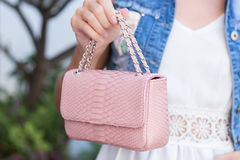 Woman hands with snakeskin python luxury bag near the swimming pool. Stylish look royalty free stock photo