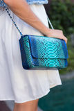 Woman hands with snakeskin python luxury bag near the swimming pool. Stylish look royalty free stock images