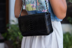 Woman hands with snakeskin python luxury bag near the swimming pool. Stylish look stock photography