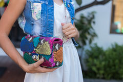 Woman hands with snakeskin python luxury bag near the swimming pool. Stylish look stock image