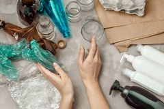 Woman hands sorting differnt types of waste. Plastic bag, crumpled paper, plastic containers, glass and bottles on the table. Management waste sorting concept royalty free stock photo