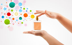 Woman hands spraying colorful bubbles from beautiful perfume bottle Royalty Free Stock Photography