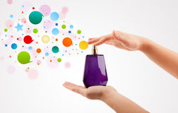 Woman hands spraying colorful bubbles from beautiful perfume bottle Stock Photo