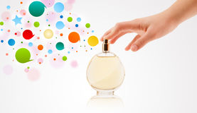 woman hands spraying colorful bubbles from beautiful perfume bottle Royalty Free Stock Image