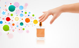 Woman hands spraying colorful bubbles from beautiful perfume bottle Royalty Free Stock Photos