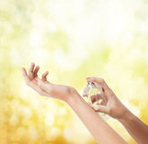 Woman hands spraying perfume. Cosmetics, body parts and beauty concept - close up of woman hands spraying perfume Royalty Free Stock Photo