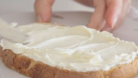 Woman hands spreading cheese on bread slice. On kitchen table video footage filmed from low angle closeup in slow motion stock video footage