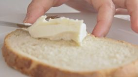 Woman hands spreading cheese cream on bread. Slice on the kitchen table. Footage video filmed from low angle in slow motion stock video