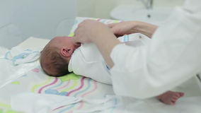 Woman hands are swaddling a newborn boy. Swaddling a newborn. The child calm stock video footage