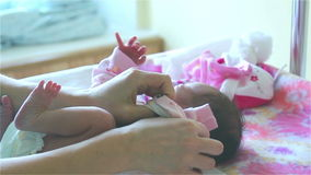 Woman hands are swaddling a newborn girl. stock video