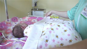 Woman hands are swaddling a newborn girl. Swaddling a newborn. Woman hands are swaddling a newborn girl. The newborn does not like to dress. Child is crying stock video footage