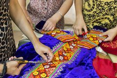 Tailoring colorful traditional wedding dresses in Uzbekistan. Woman hands tailoring local wedding dresses in the city of Nukus, Uzbekistan Royalty Free Stock Photo