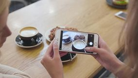 Woman hands taking food photo on mobile phone at cafe closeup. Girls making photos of coffee indoors stock footage
