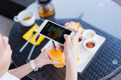 Woman hands taking food photo by mobile phone. Food photography. Delicious breakfast. Royalty Free Stock Photo