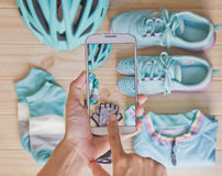 Woman hands taking photo of top view of sport equipment in pastel colour by mobile phone. Top view of sport equipment in pastel colour: helmet, shoes, biking Stock Photo
