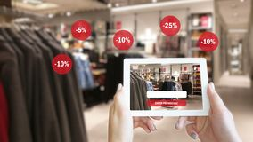 Woman hands taking a tablet in shopping mall with blurred image of clothes shop. stock photography