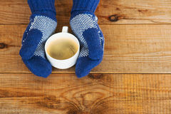 Woman hands in teal gloves are holding a mug with hot coffee or Royalty Free Stock Photo