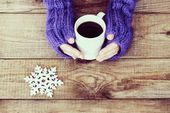 Woman hands in teal gloves are holding a mug with hot coffee or Royalty Free Stock Photography