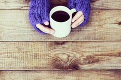 Woman hands in teal gloves are holding a mug with hot coffee or Stock Image