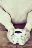 Woman hands in teal gloves are holding a mug with hot coffee or Stock Photography