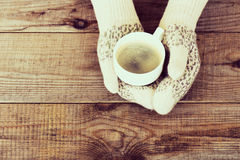 Woman hands in teal gloves are holding a mug with hot coffee or Royalty Free Stock Images