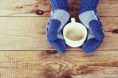 Woman hands in teal gloves are holding a mug with hot coffee or Stock Photo