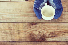 Woman hands in teal gloves are holding a mug with hot coffee or Stock Photos