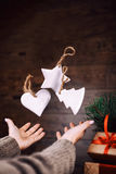 Woman hands throws up homemade Christmas tree toys. dark background. Selective focus. Stock Images