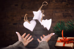 Woman hands throws up homemade Christmas tree toys. dark background. Selective focus. Royalty Free Stock Photography