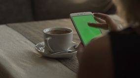 Woman hands touching on green screen mobile phone on background coffee cup. On saucer standing at table in cafe. Woman using green screen smartphone. Mockup stock video