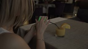 Woman hands touching green screen mobile phone on background orange juice glass. Standing at table in cafe. Woman using green screen smartphone. Mockup chroma stock footage