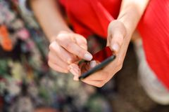 Woman hands touching touch screen of a smart phone outdoors Royalty Free Stock Photos